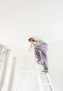 Man climbing ladder indoorsの写真素材 [FYI02150025]