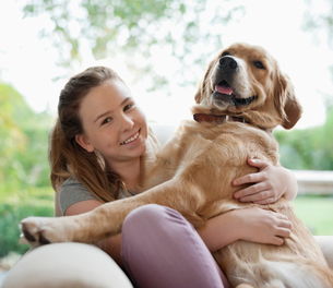 Smiling girl hugging dog on sofaの写真素材 [FYI02150113]