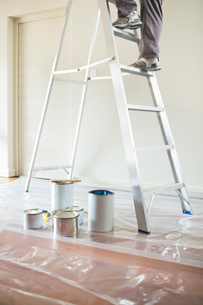 Man climbing ladder to paint roomの写真素材 [FYI02150131]