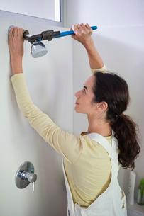 Woman working on shower head in bathroomの写真素材 [FYI02150156]
