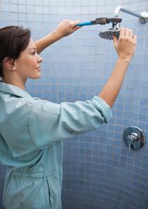 Female plumber working on shower head in bathroomの写真素材 [FYI02150240]