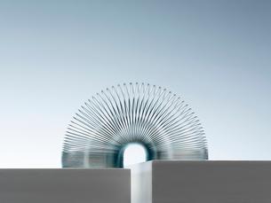 Metal slinky spanning space between blocksの写真素材 [FYI02150252]