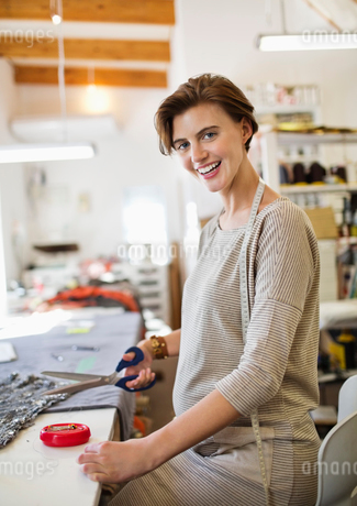 Dressmaker cutting fabric in studioの写真素材 [FYI02150426]