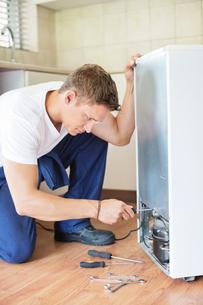 Repairman working on appliance in kitchenの写真素材 [FYI02150488]