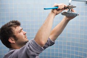 Plumber working on shower head in bathroomの写真素材 [FYI02150501]