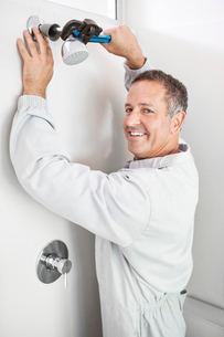 Plumber working on shower head in bathroomの写真素材 [FYI02150517]