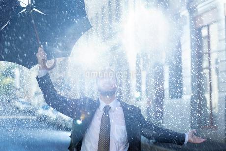 Enthusiastic man with broken umbrella in rainの写真素材 [FYI02150602]