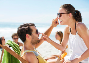 Couple applying sunscreen to each other's nose on beachの写真素材 [FYI02150630]