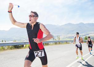 Runner spraying himself with water in raceの写真素材 [FYI02150678]