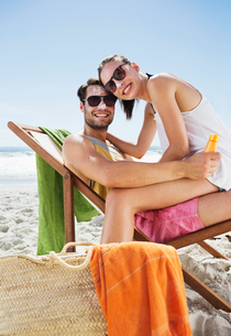 Portrait of smiling couple with sunscreen on noses at beachの写真素材 [FYI02150742]