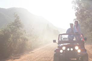 Friends driving sport utility vehicle on dirt roadの写真素材 [FYI02150764]
