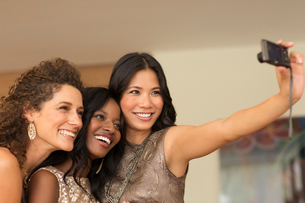 Women taking picture together indoorsの写真素材 [FYI02150784]
