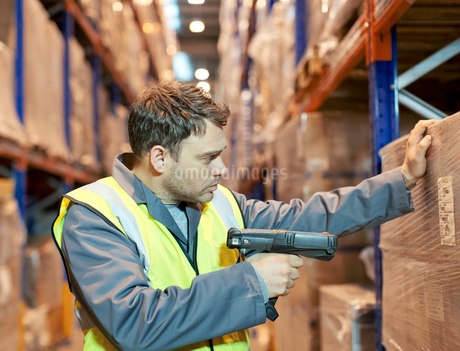 Worker scanning boxes in warehouseの写真素材 [FYI02150925]