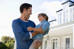 Father and son smiling outside houseの写真素材 [FYI02150985]