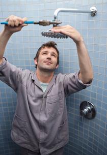 Plumber working on shower head in bathroomの写真素材 [FYI02151058]