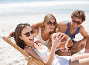 Smiling friends with football on beachの写真素材 [FYI02151351]