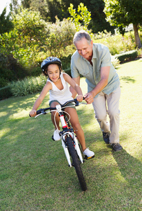 Older man teaching granddaughter to ride bicycleの写真素材 [FYI02151355]