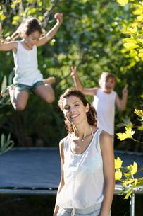 Mother standing by children on trampolineの写真素材 [FYI02151425]