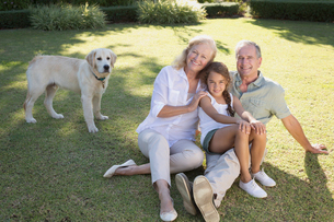 Older couple smiling with granddaughter in backyardの写真素材 [FYI02151460]