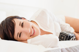 Portrait of smiling woman with vintage camera in bedの写真素材 [FYI02151530]