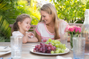 Mother and daughter smiling at table outdoorsの写真素材 [FYI02151668]
