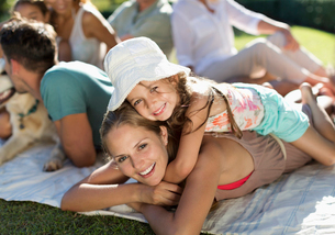 Mother and daughter relaxing in grass with familyの写真素材 [FYI02151701]