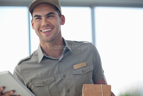 Delivery boy smiling with packageの写真素材 [FYI02151712]