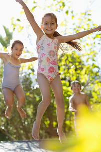 Children jumping on trampoline outdoorsの写真素材 [FYI02151771]