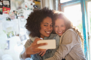 Women taking picture together in bedroomの写真素材 [FYI02151866]