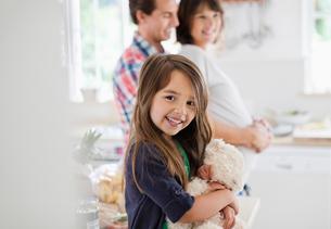 Girl holding teddy bear in kitchenの写真素材 [FYI02151869]