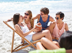 Happy friends with football hanging out at beachの写真素材 [FYI02151918]
