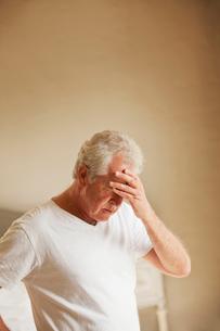 Senior man holding head in painの写真素材 [FYI02151953]