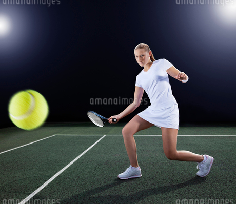 Tennis player hitting ball on courtの写真素材 [FYI02151973]