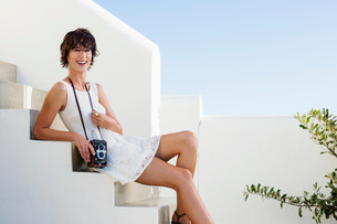 Portrait of smiling woman with vintage camera on stairsの写真素材 [FYI02152030]