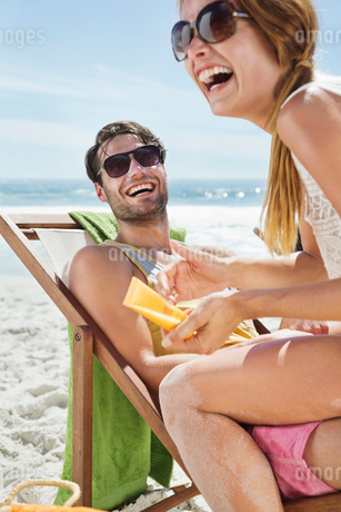 Happy couple with sunscreen at beachの写真素材 [FYI02152052]