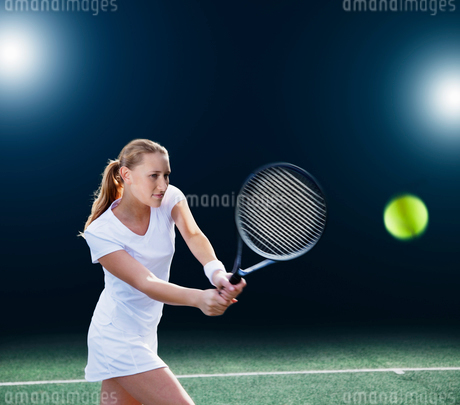 Tennis player hitting ball on courtの写真素材 [FYI02152102]