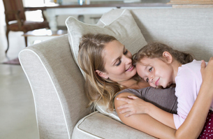 Mother and daughter relaxing on sofaの写真素材 [FYI02152147]
