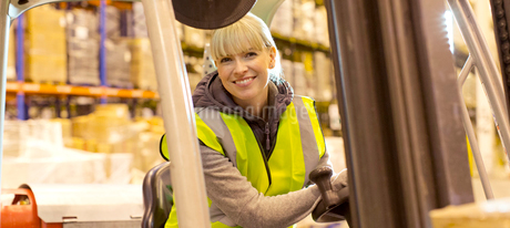 Worker operating forklift in warehouseの写真素材 [FYI02152164]