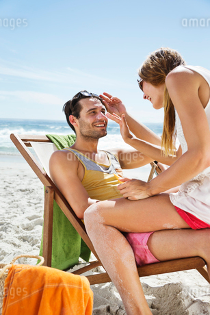 Woman applying sunscreen to man's nose at beachの写真素材 [FYI02152167]