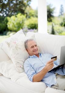Senior man shopping online on patio sofaの写真素材 [FYI02152216]