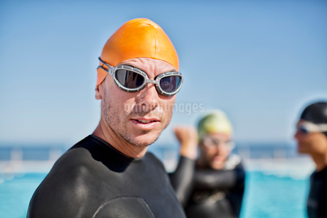 Triathletes in wetsuits wearing goggles and capの写真素材 [FYI02152396]