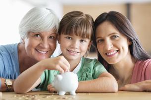 Three generations of women filling piggy bankの写真素材 [FYI02152406]