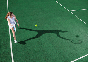 Tennis player casting shadow on courtの写真素材 [FYI02152416]