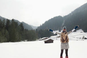 Carefree woman with arms outstretched in snowy fieldの写真素材 [FYI02152452]