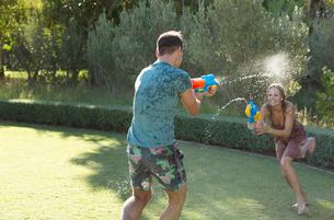 Couple playing with water guns in backyardの写真素材 [FYI02152574]