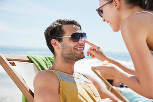 Woman applying sunscreen to man's nose at beachの写真素材 [FYI02152603]