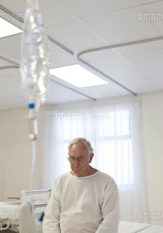 Older patient sitting on bed in hospital roomの写真素材 [FYI02152653]