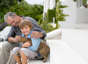 Older man and grandson petting cat on stepsの写真素材 [FYI02152744]