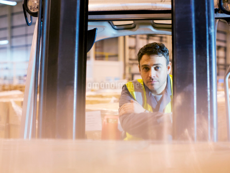 Worker operating forklift in warehouseの写真素材 [FYI02152809]