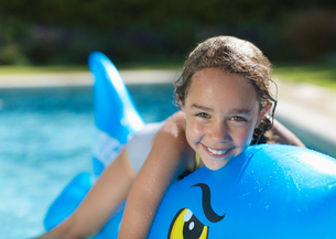 Girl riding inflatable toy in swimming poolの写真素材 [FYI02152842]